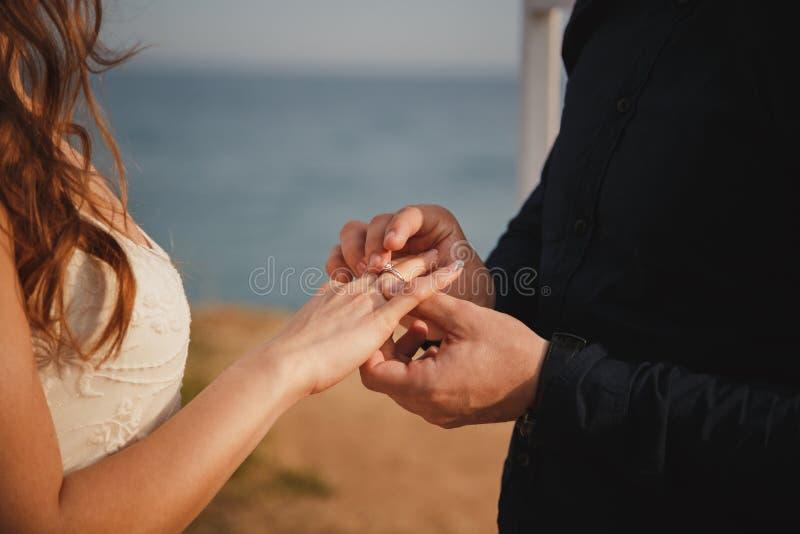 人在他的新娘` s手上把婚戒,关闭放  室外海滩婚礼仪式、时髦的新郎和新娘站立n 免版税图库摄影