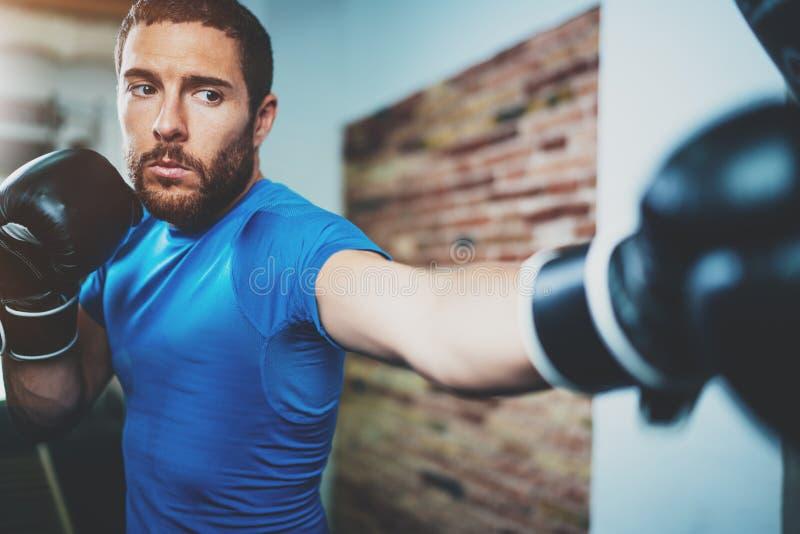 年轻人在健身健身房的拳击锻炼在被弄脏的背景 艰苦训练运动的人 脚踢拳击概念 水平 免版税库存图片