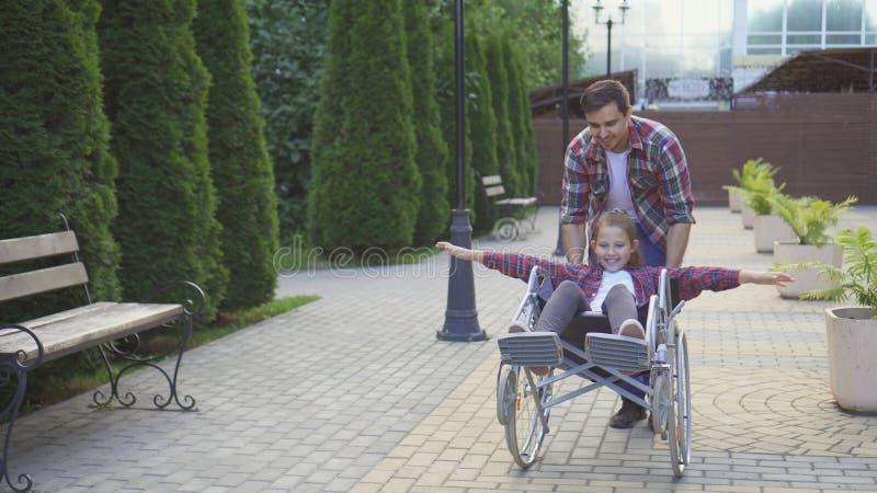 人在公园滚动一个轮椅的一个愉快的少年 免版税库存图片