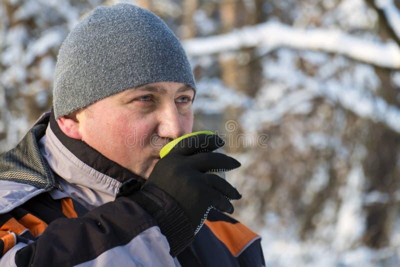 人在冬天森林里喝从钢杯子的热的茶 免版税图库摄影