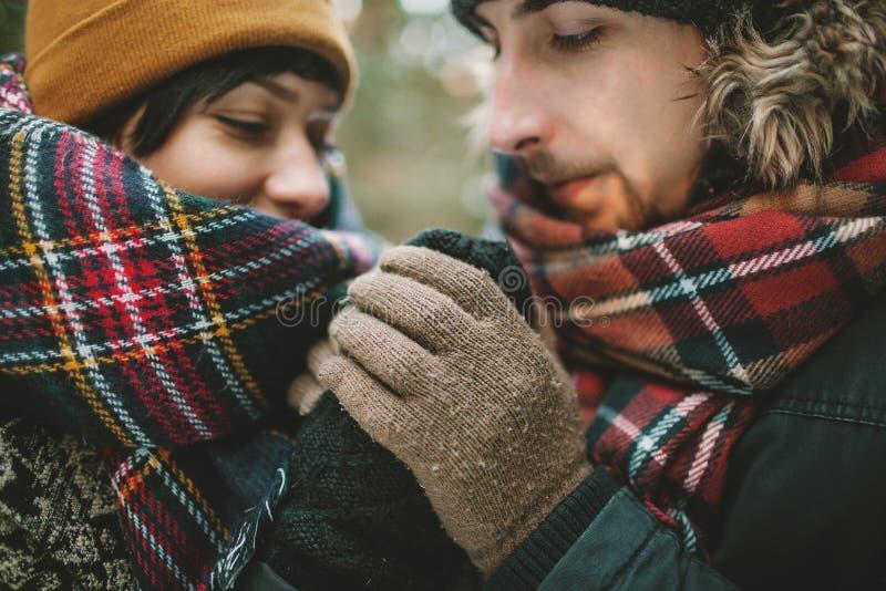 年轻人在冬天森林里握他的女朋友手 免版税图库摄影