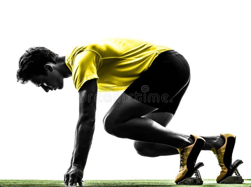 年轻人在出发台剪影的短跑选手赛跑者 免版税图库摄影