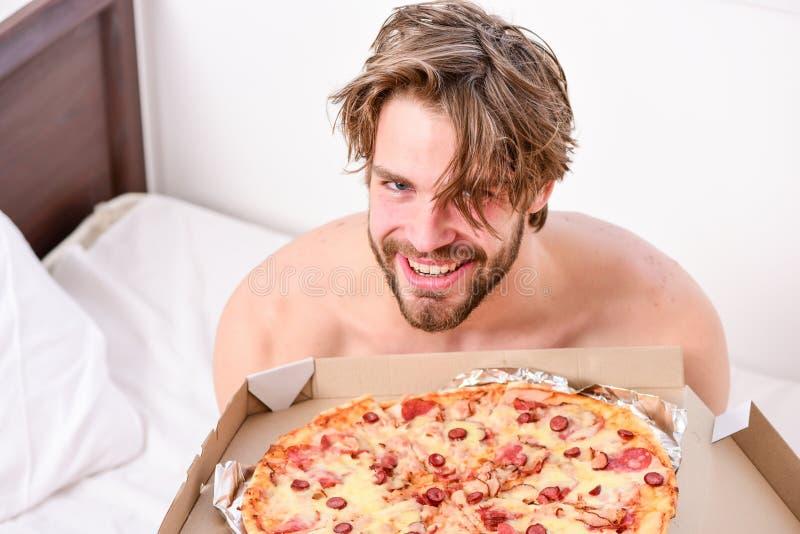 人在卧室或旅馆客房拿着薄饼箱子坐床 在家是在一栋明亮的公寓的床上吃鲜美的学生 免版税库存照片