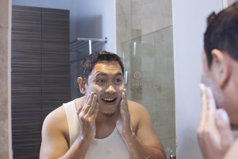 人在卫生间里洗他的面孔 免版税库存照片