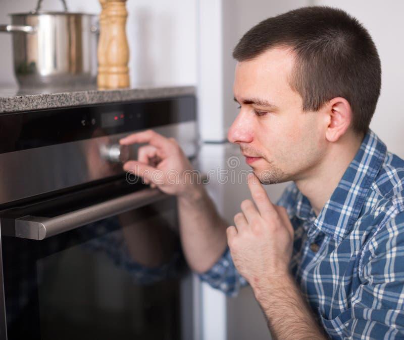 年轻人在厨房里控制烤箱 免版税库存图片