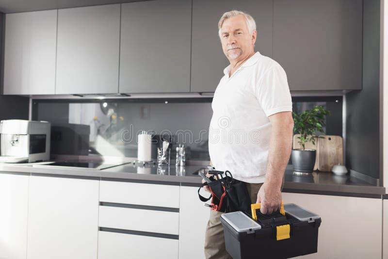 人在厨房 他有一个黑工具箱在他的手 在他旁边是工具箱 库存图片