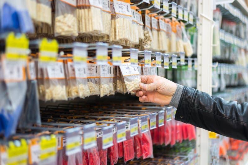 人在商店选择定缝销钉 免版税图库摄影