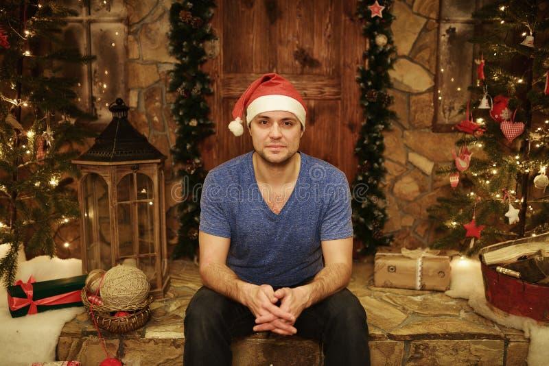 年轻人在圣诞老人盖帽在家坐步装饰的圣诞节样式 库存图片