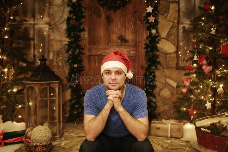 年轻人在圣诞老人盖帽在家坐步装饰的圣诞节样式 库存照片