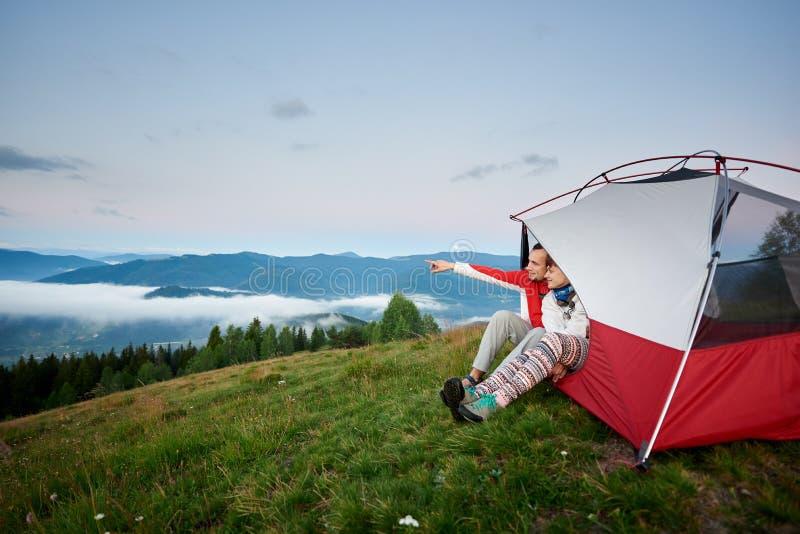 人在坐在帐篷的距离显示他的手靠近妇女从反对山 免版税库存图片