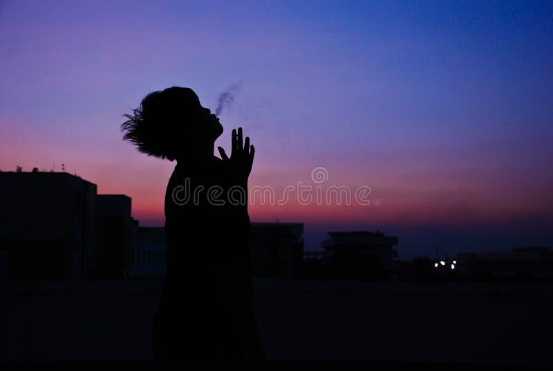人在大厦顶部的烟香烟剪影  免版税库存图片