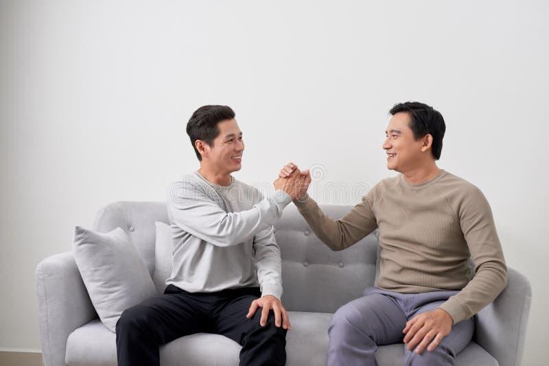 人在家坐沙发和握手与朋友 多种族人友谊 图库摄影