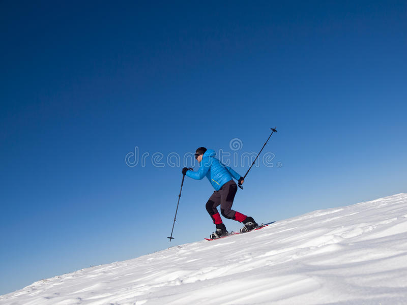 人在山的雪靴跳 库存照片