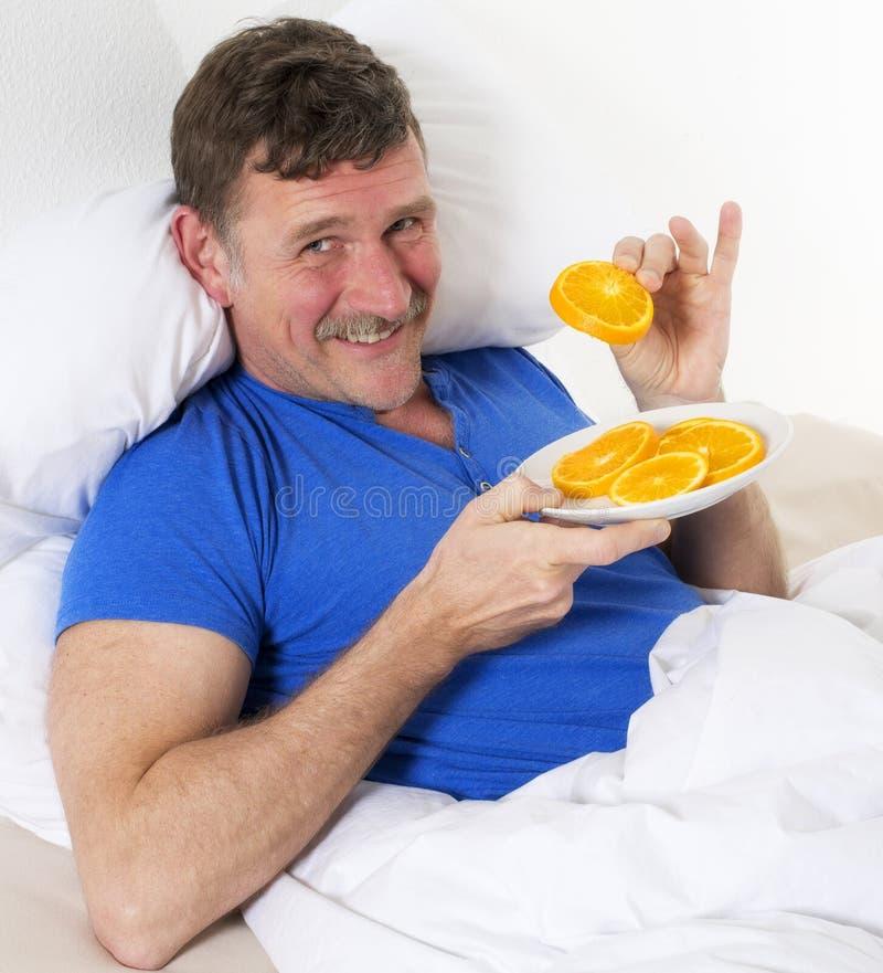 人在床上用桔子 图库摄影