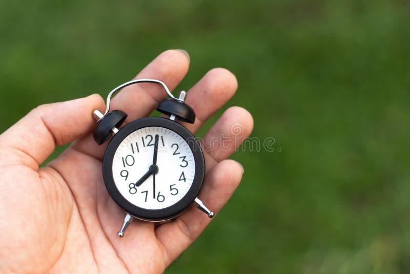 人在手上的拿着一个闹钟 免版税库存图片