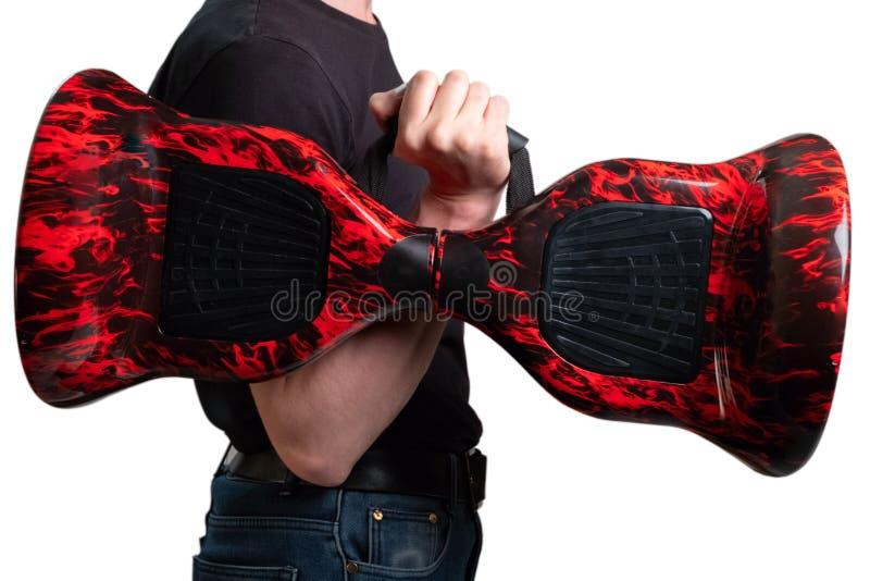 人在手上的拿着现代红色电微型翱翔委员会滑行车 趋向新的运输技术 自平衡两 免版税库存照片