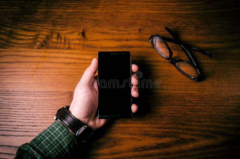 人在手机屏幕上的手接触在一张木桌上的 业务组象征性人的情形 图库摄影