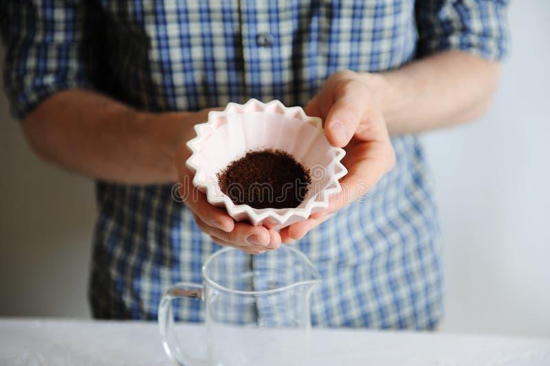 人在手桃红色陶瓷origami滴管举行紧密匿名 在纸过滤器的碾碎的咖啡 手工酿造 库存图片