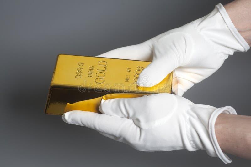 人在拿着金锭的白色手套的` s手 免版税库存图片