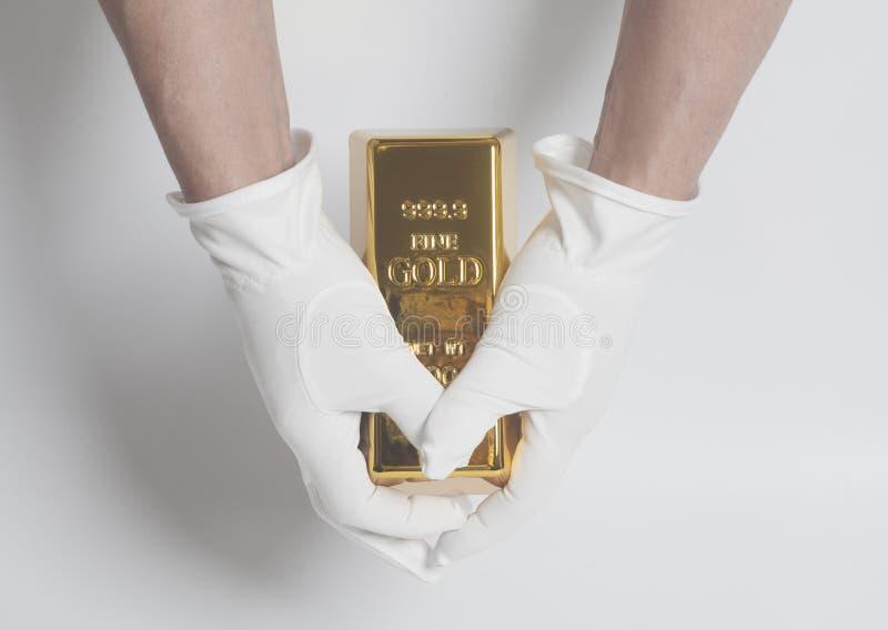 人在拿着金锭的白色手套的` s手 库存照片