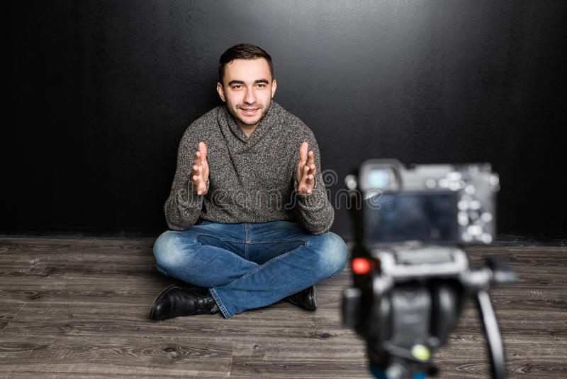 年轻人在数字照相机的焦点对概念的墙壁关于录影blogging 库存图片