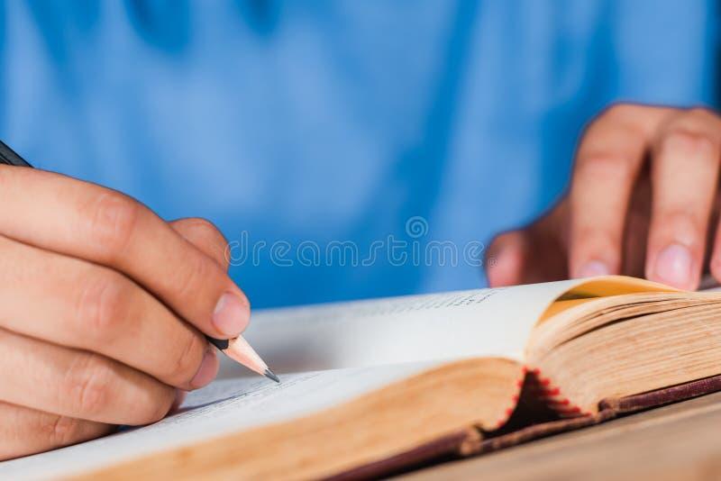 人在旧书的文字笔记 免版税库存照片