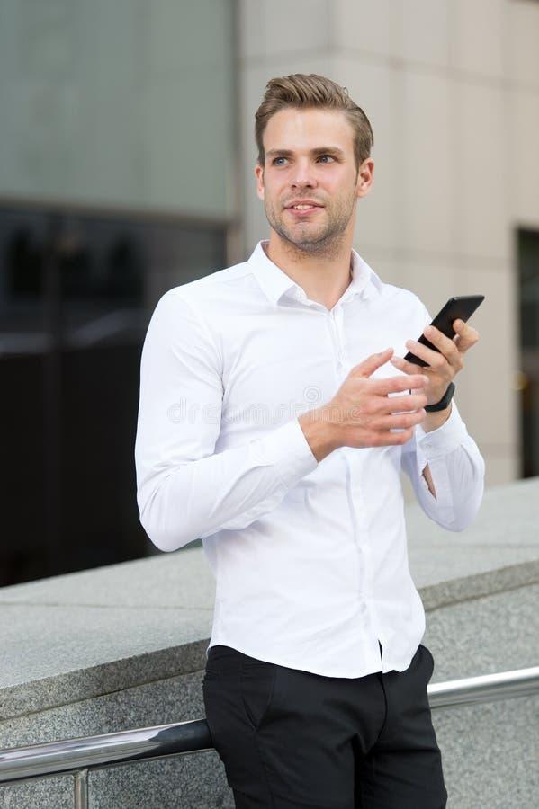 人在早晨都市背景中的检查电子邮件 商人送消息或发短信与智能手机 英俊的人 免版税库存图片