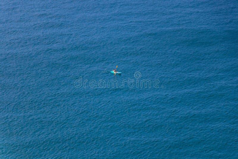 人在普吉府,泰国用浆划在海的皮船 库存图片