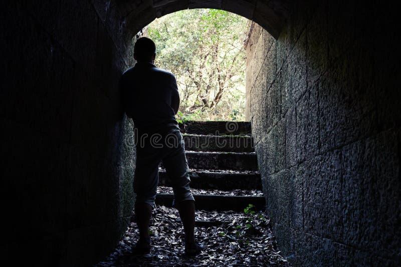 人在有发光的末端的黑暗的石隧道站立 库存图片