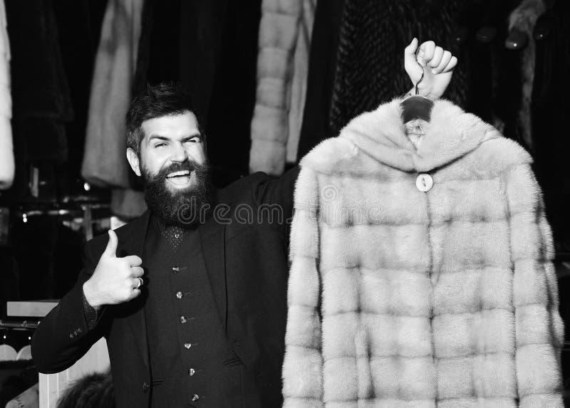 人在有毛皮的商店拿着米黄毛茸的外套在背景 冬天衣物概念 有时髦的出现的强壮男子与 库存图片