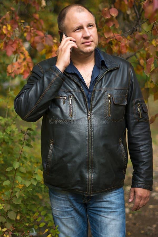 人在有电话的秋天公园 库存图片