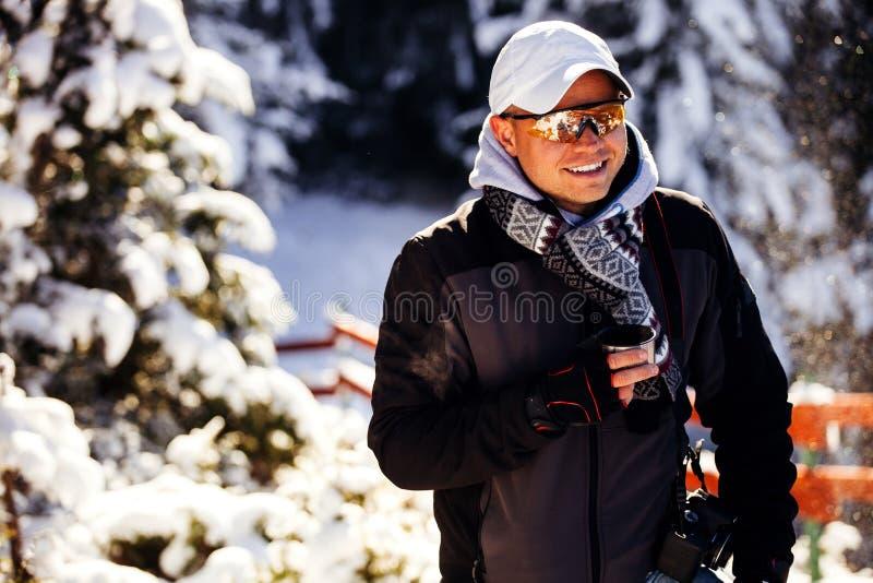 人在有雪的冷的冬天森林里喝茶 免版税库存图片