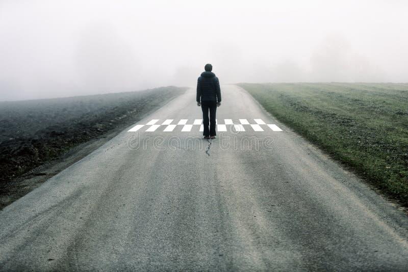人在有雾的柏油路站立 免版税库存照片