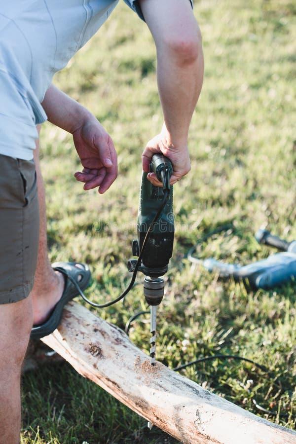 人在木材的钻孔,当工作在庭院里时 图库摄影