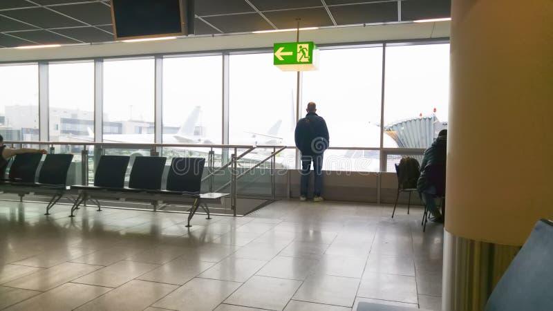 人在机场看窗口并且观看航空器的飞行 库存图片