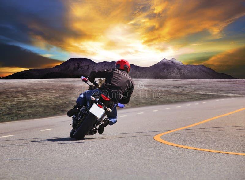 年轻人在柏油路曲线w的骑马摩托车背面图  免版税库存图片