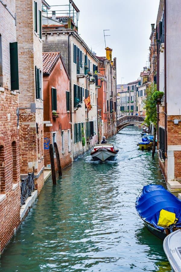 人在水路河水运河的帆船在大厦和人之间在背景中的横断步行桥在威尼斯 免版税库存照片