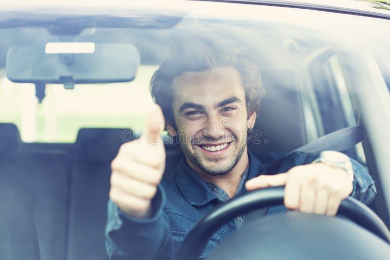 年轻人在汽车的赞许姿态 图库摄影