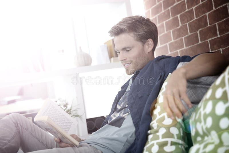 年轻人在沙发的阅读书 免版税库存照片