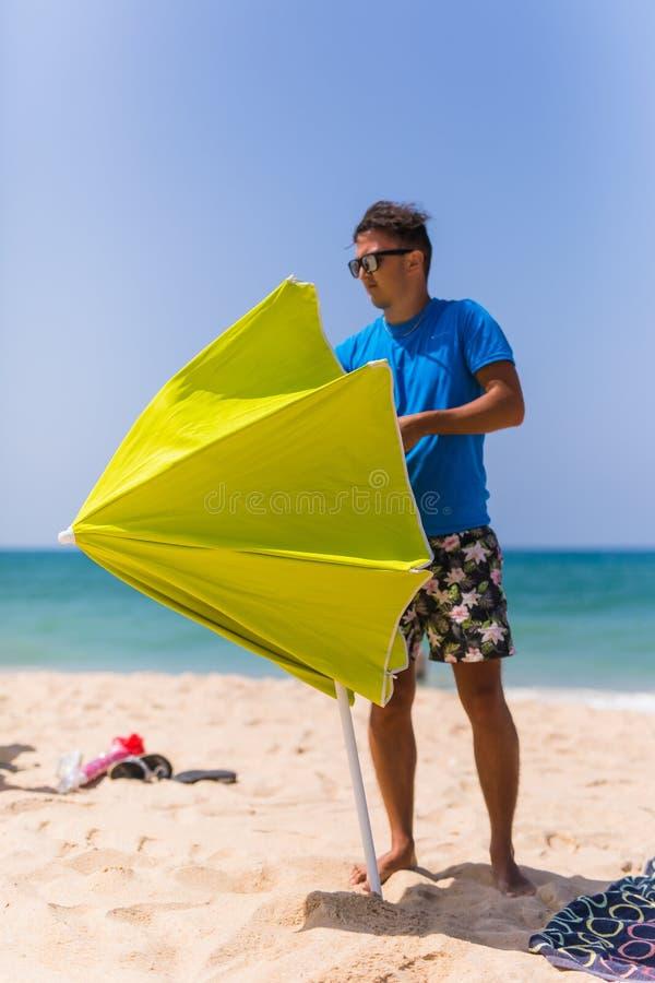 年轻人在沙子太阳伞安装在海滩在海洋附近 库存图片
