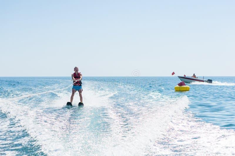 年轻人在波浪的滑水竞赛滑动在海,海洋 健康生活方式 正面人的情感,感觉 免版税库存照片
