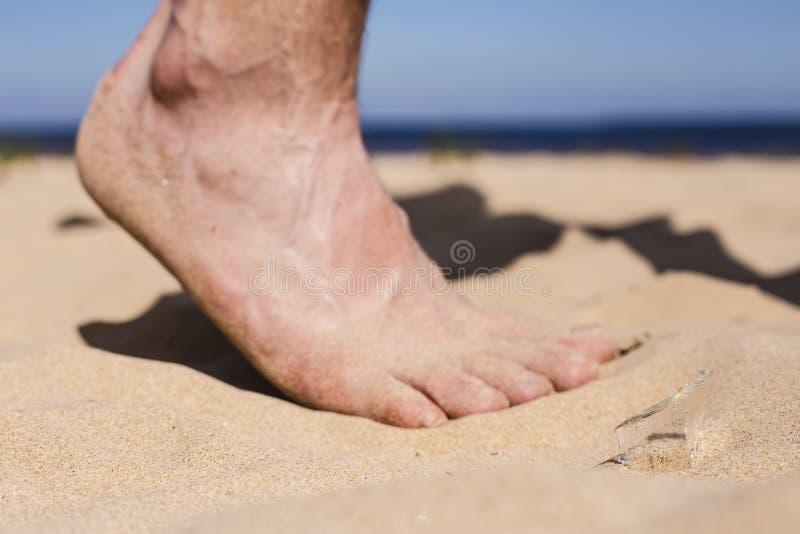 人在海滩和跨步的风险去在残破的玻璃瓶裂片  免版税图库摄影