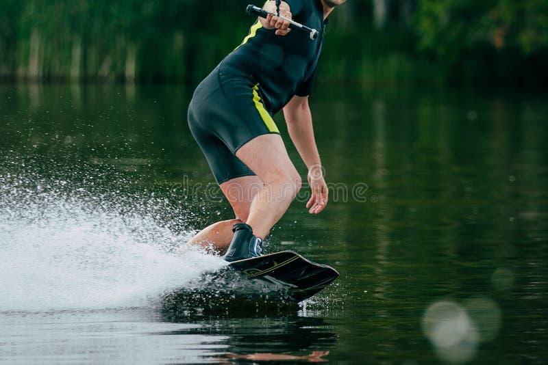 年轻人在湖乘坐wakeboard 免版税库存照片