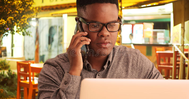 黑人在电话谈话在餐馆,当研究他的膝上型计算机时 库存照片