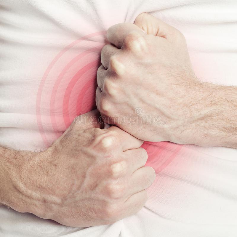 人在痛苦或消化不良中的握他的胃 免版税库存照片