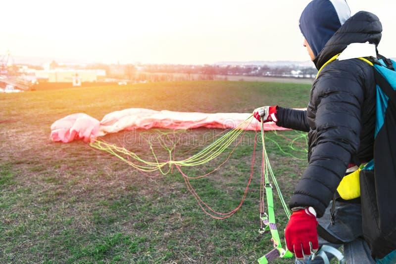 人在登陆折叠降伞在绿色领域以后 免版税库存照片