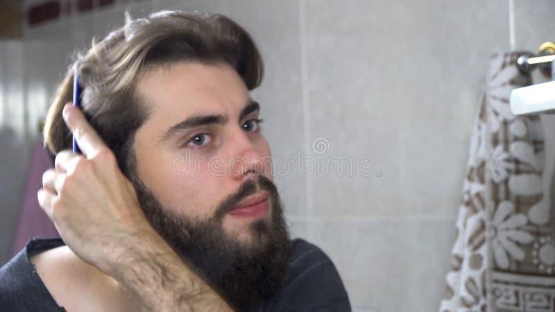 人在看在镜子和修理他的头发的卫生间里 掠过他的头发的英俊的人画象在卫生间里 免版税图库摄影
