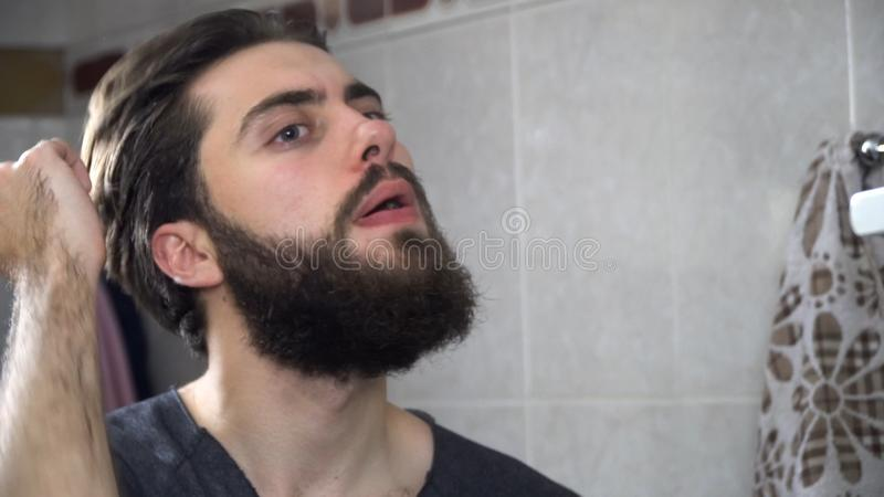 人在看在镜子和修理他的头发的卫生间里 掠过他的头发的英俊的人画象在卫生间里 库存图片