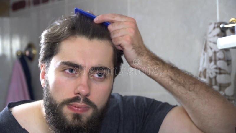 人在看在镜子和修理他的头发的卫生间里 掠过他的头发的英俊的人画象在卫生间里 免版税库存图片