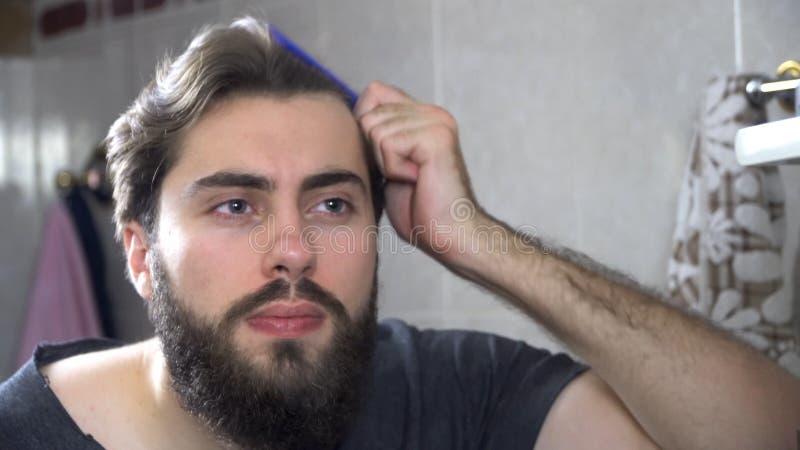 人在看在镜子和修理他的头发的卫生间里 掠过他的头发的英俊的人画象在卫生间里 图库摄影